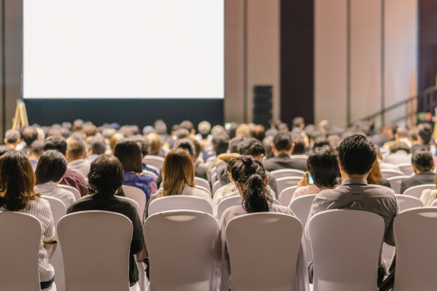 rear-view-audience-listening-speakers-stage-conference-hall-seminar-meeting_41418-3412